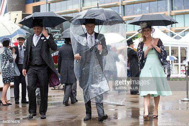 Racegoers shelter from the rain on the first day of the Royal Ascot horse racing meet in Ascot west of London on June 14 2016 / AFP / JUSTIN TALLIS