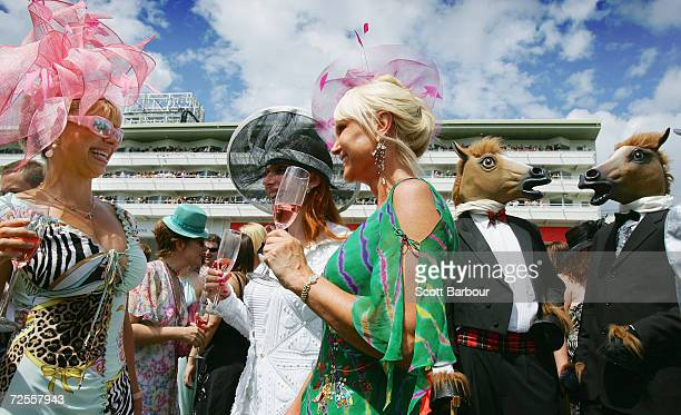 Racegoers sip champagne as they wait for the next race during Ladies Day at the Epsom Festival at Epsom Downs racecourse on June 3 2005 in Surrey...