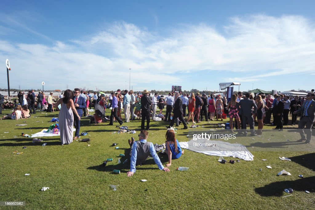 Racegoers sit on the grass during Melbourne Cup Day at Flemington Racecourse in Melbourne, Australia, on Tuesday, Nov. 5, 2013. The Melbourne Cup, marketed as the race that stops the nation, is Australias premier thoroughbred horse racing event. Photographer: Carla Gottgens/Bloomberg via Getty Images