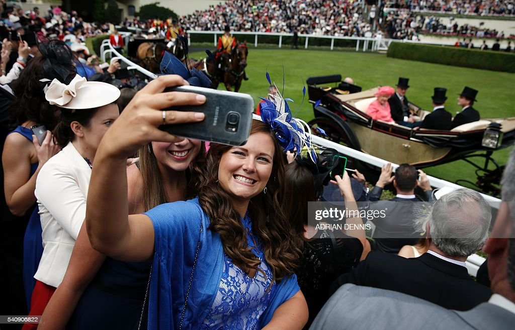 Racegoers take a selfie as Britain's Queen Elizabeth II and The Duke of Edinburgh arrive in the parade ring in a carriage for day four at Royal Ascot...