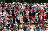Racegoers take photographs as Queen Elizabeth II arrives in the parade ring by horse drawn carriage during Ladies Day at Royal Ascot racecourse on...