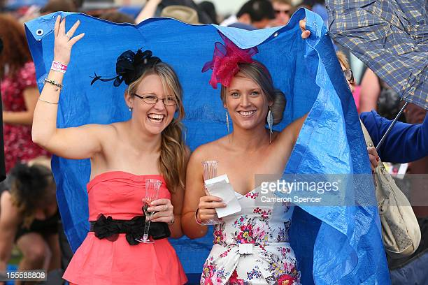 Racegoers try to avoide the rain on Melbourne Cup Day at Flemington Racecourse on November 6 2012 in Melbourne Australia