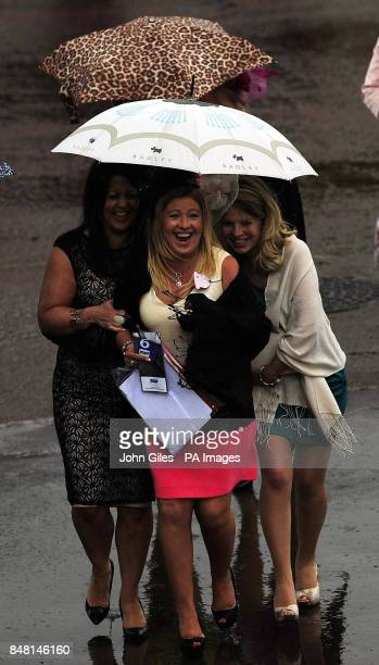 Racegoers trying to keep dry as heavy rain showers fall on Mid Summer Raceday during the June Meeting at York Racecourse York