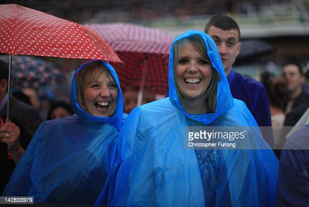 Racegoers use ponchos to shelter from the rain during Ladies Day at the Aintree Grand National meeting on April 13 2012 in Aintree England Friday is...