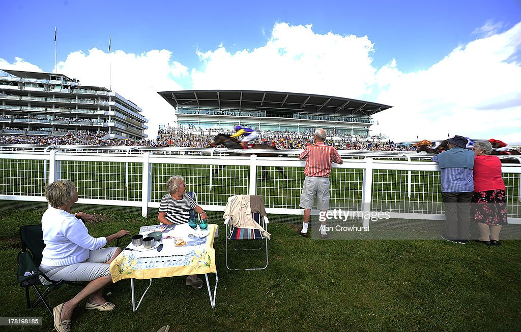 Racegoers watach as <a gi-track='captionPersonalityLinkClicked' href=/galleries/search?phrase=Jamie+Spencer&family=editorial&specificpeople=208902 ng-click='$event.stopPropagation()'>Jamie Spencer</a> riding Hopes N Dreams win The John Akehurst Handicap Stakes at Epsom racecourse on August 27, 2013 in Epsom, England.