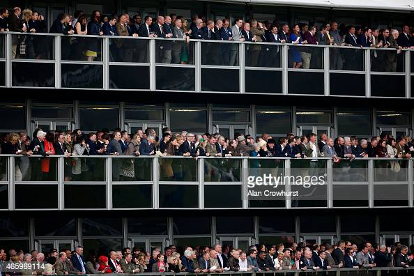 Racegoers watch from the hospitality grandstand at Cheltenham racecourse on March 12 2015 in Cheltenham England