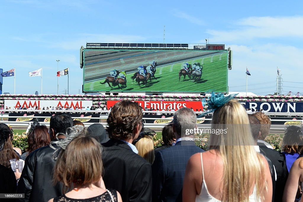 Racegoers watch race 7 The Emirates Melbourne Cup on a giant screen above advertising for AAMI insurance, Emirates Airlines and Crown during Melbourne Cup Day at Flemington Racecourse in Melbourne, Australia, on Tuesday, Nov. 5, 2013. The Melbourne Cup, marketed as the race that stops the nation, is Australias premier thoroughbred horse racing event. Photographer: Carla Gottgens/Bloomberg via Getty Images