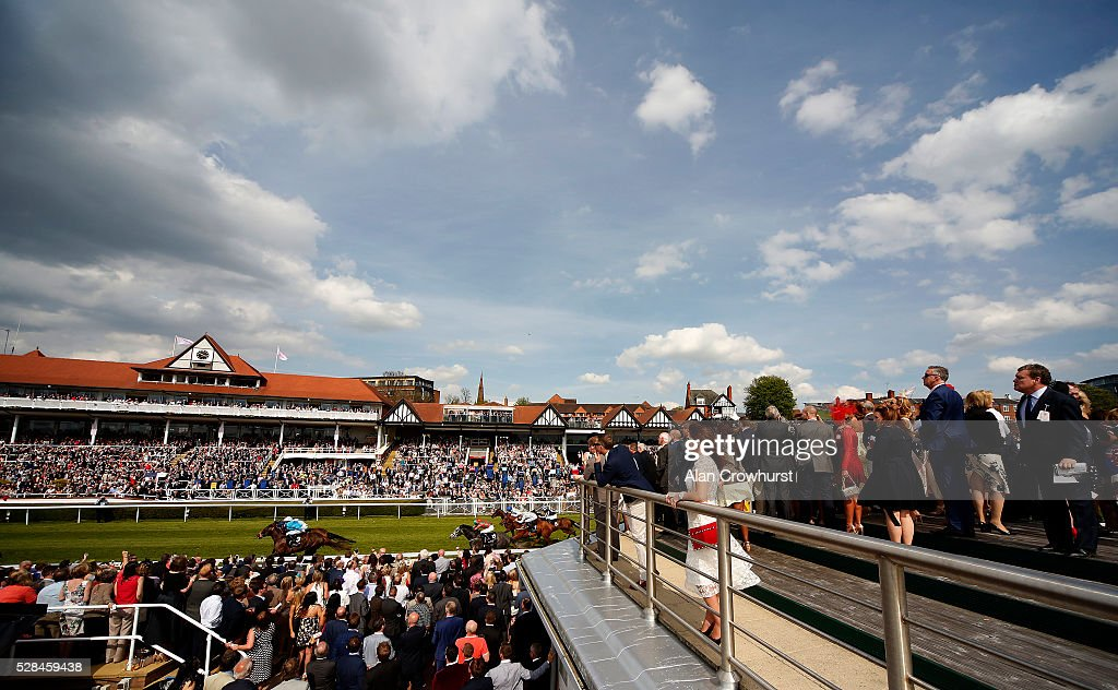 Racegoers watch the action as runners approach the finish at Chester racecourse on May 5, 2016 in Chester, England.