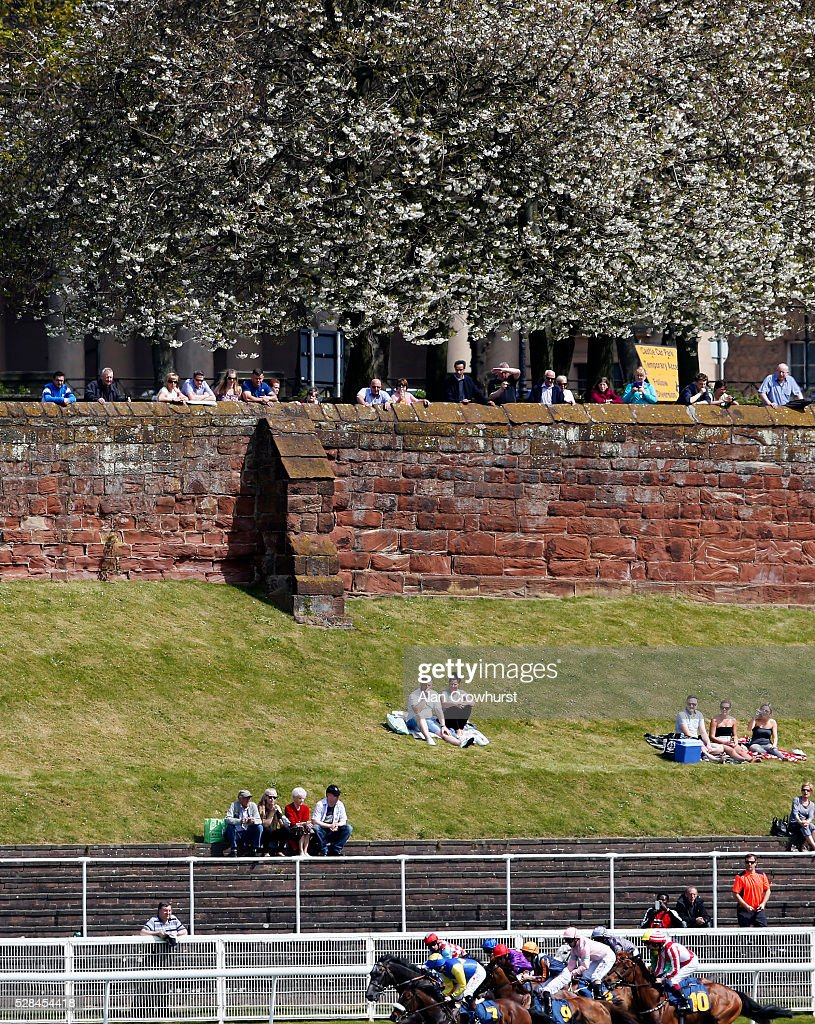 Racegoers watch the action over the Roman wall at Chester racecourse on May 5, 2016 in Chester, England.