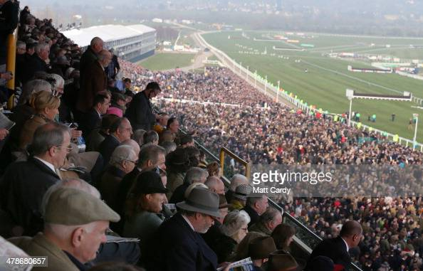 Racegoers watch the Cheltenham Gold Cup from the stands on the final day of the Cheltenham Festival on March 14 2014 in Cheltenham England Thousands...
