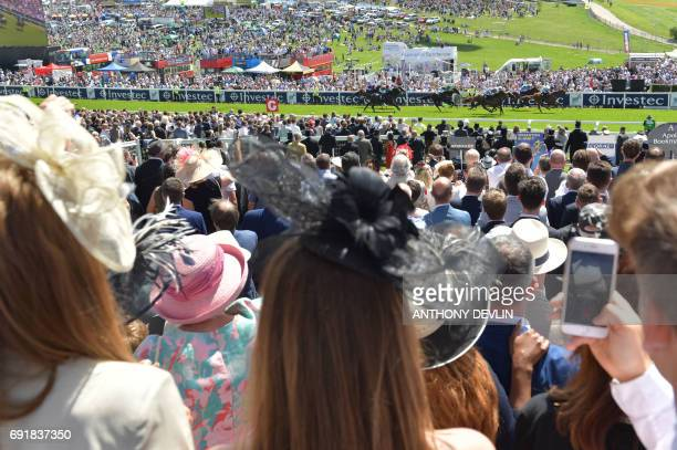 Racegoers watch the first race of the day on the second day of the Epsom Derby Festival in Surrey southern England on June 3 2017 / AFP PHOTO /...