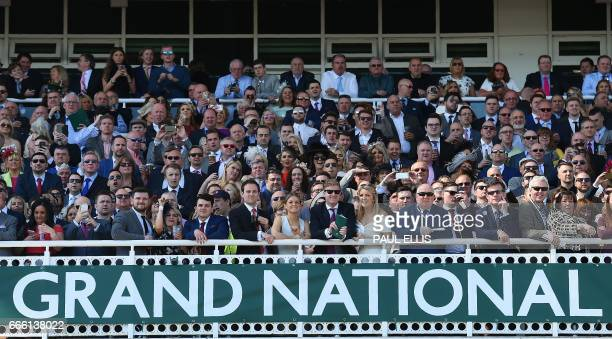 Racegoers watch the first race of the final day of the Grand National Festival horse race meeting at Aintree Racecourse in Liverpool northern England...