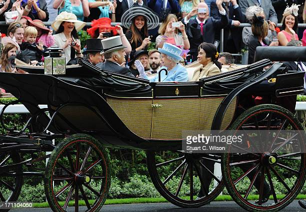 Racegoers wave at Queen Elizabeth II Prince El Hassan Bin Talal Princess Sarvath El Hassan and John Warren as they arrive with the Royal Procession...