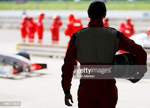 Racer carrying helmet on sidelines