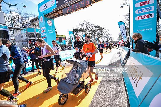 A racer on the finish line with a baby buggy of the race during Half Marathon on March 6 2016 in Paris France