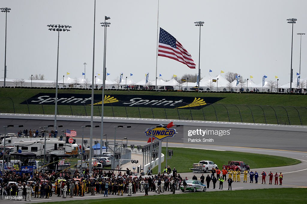 Racers and crew members stand at attention during the national anthem during the NASCAR Camping World Truck Series SFP 250 at Kansas Speedway on April 20, 2013 in Kansas City, Kansas.