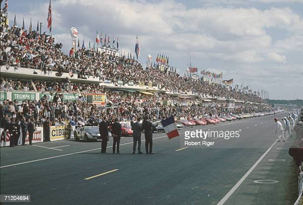 Racers from many nations watch and wait for the French flag to drop indicating that they may run to their cars and start racing in the 24 Hours of Le...