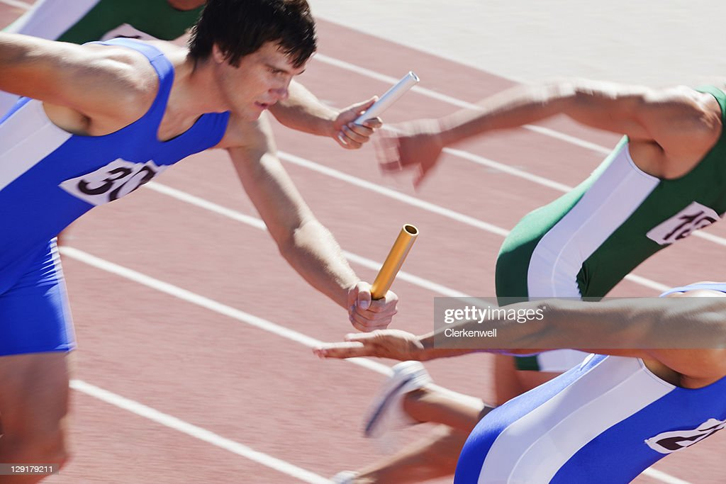 Racers running on track with relay baton : Stock Photo