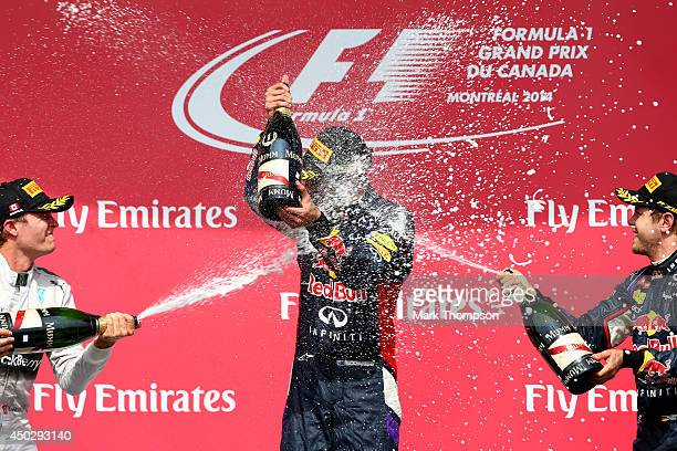 Racewinner Daniel Ricciardo of Australia and Infiniti Red Bull Racing is sprayed with champagne by second placed Nico Rosberg of Germany and Mercedes...