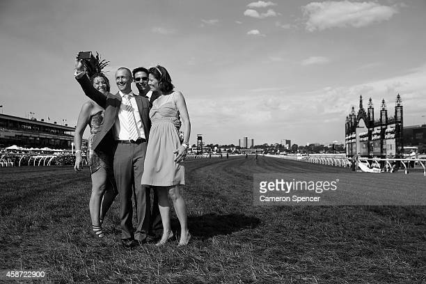 Racgoers take a photograph on Melbourne Cup Day at Flemington Racecourse on November 4 2014 in Melbourne Australia