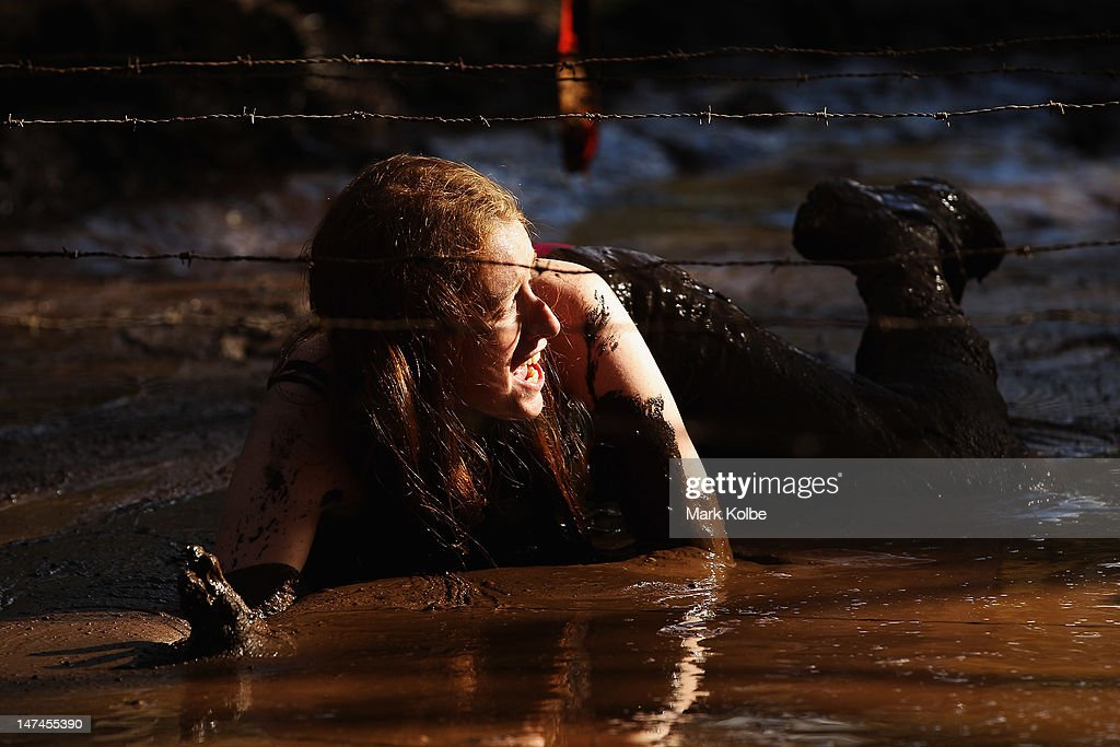 Rachael Martin crawls through the 'Mud Bath' obstacle as she competes in the Tough Bloke Challenge at the Cataract Scout Park on June 30, 2012 in Sydney, Australia.