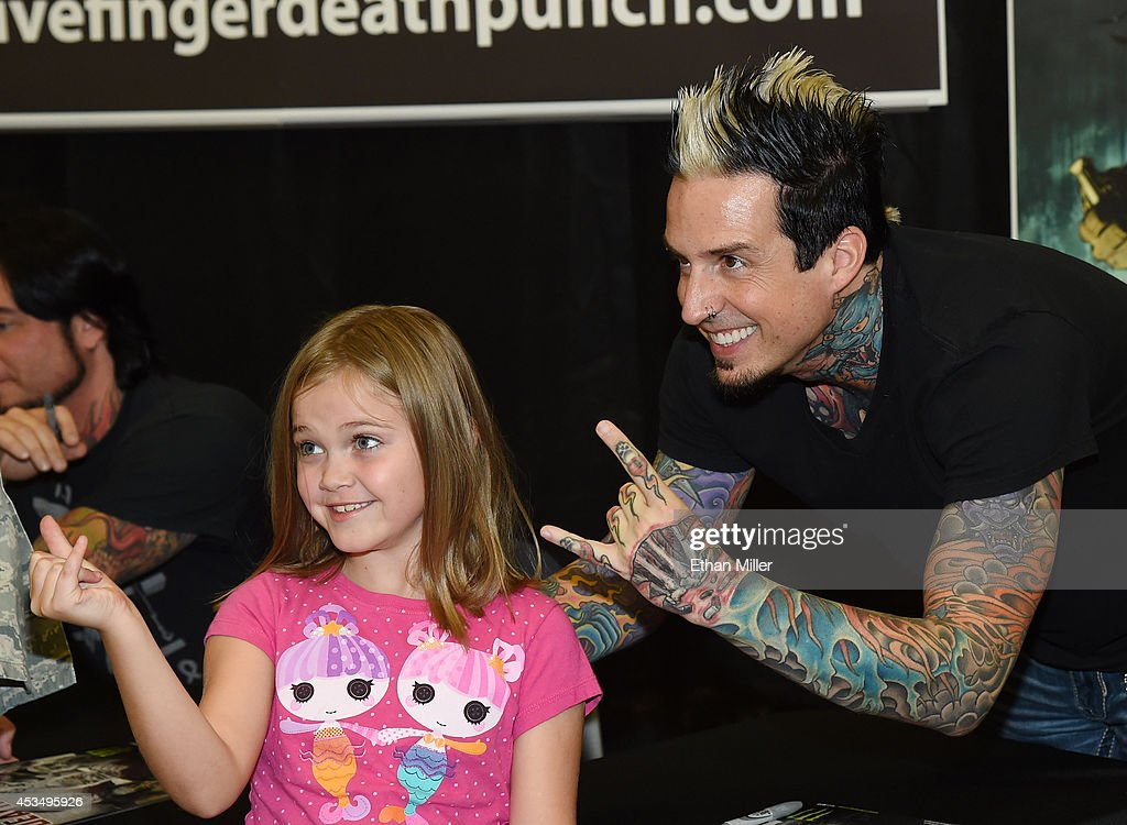 Rachel Allen, 7, poses for a photo with drummer Jeremy Spencer of Five Finger Death Punch at Nellis Air Force Base as the band highlights its campaign to raise awareness about veterans suffering from post-traumatic stress disorder (PTSD), in part by launching the video 'Wrong Side of Heaven,' that deals with the subject on August 11, 2014 in Las Vegas, Nevada.