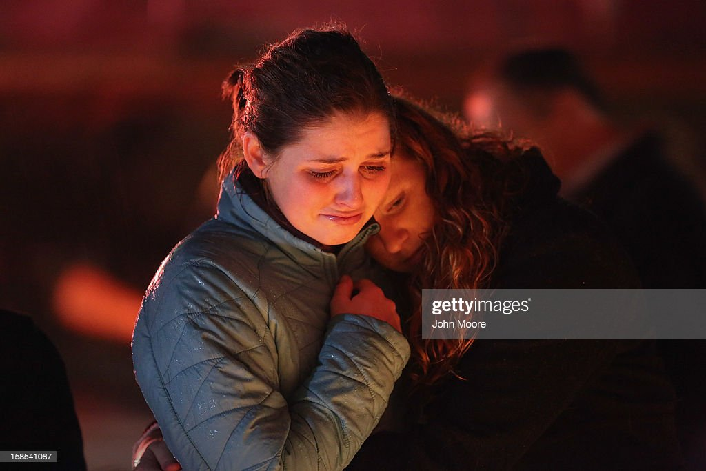 Rachel Berger (L), and Greta Waag embrace while visiting a makeshift memorial for shooting victims on December 18, 2012 in Newtown, Connecticut. Funeral services were held in Newtown Tuesday for Jessica Rekos and James Mattioli, both age six, four days after 20 children and six adults were killed at Sandy Hook Elementary School.
