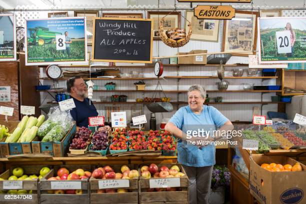 Rachel Easton laughs while her husband Harry Easton speaks at their produce stand inside of Bethesda Farm Women's Market on April 29 2017 in Bethesda...