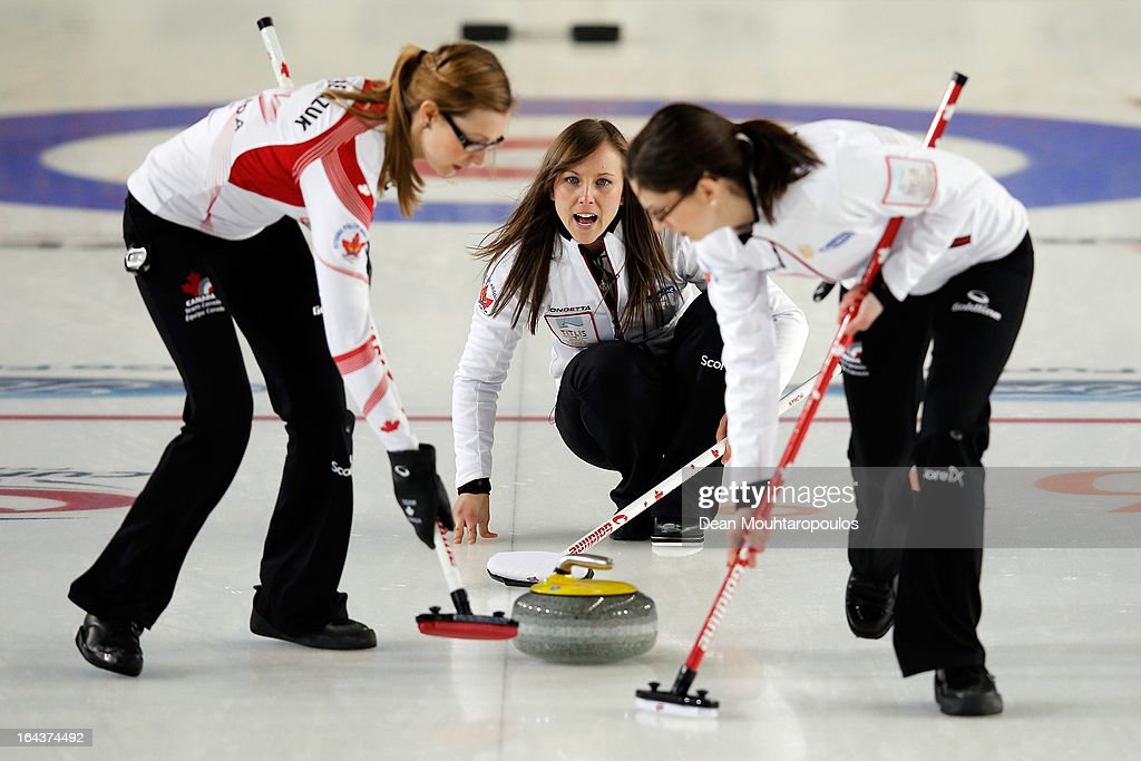 Rachel Homan (C) of Canada yells instructions after she throws a stone as Lisa Weagle (R) and Alison Kreviazuk (L) sweep during the 3rd and 4th Play-Off match between USA and Canada on Day 8 of the Titlis Glacier Mountain World Women's Curling Championship at the Volvo Sports Centre on March 23, 2013 in Riga, Latvia.