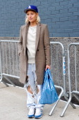 Rachel Wang is seen outside the Altuzarra show wearing a Zara coat with Ashish jeans and bag on February 8 2014 in New York City