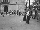 Racially mixed students playing softball at Crane Junior High during height of Brown vs Board of Education