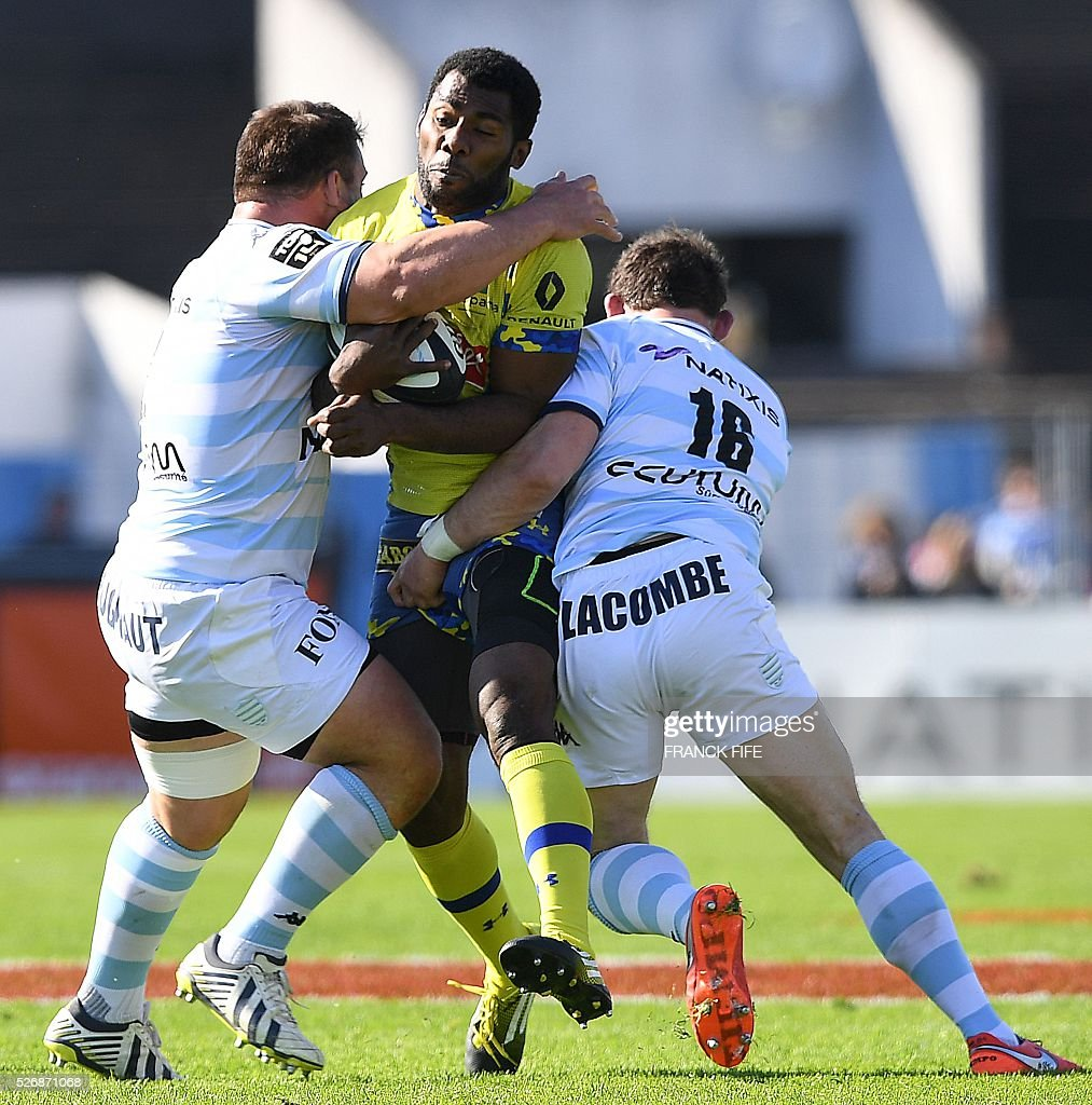 Racing 92 French prop Julien Brugnaut (L) and Racing 92 French hooker Virgile Lacombe (R) tackle Clermont's Fidjian winger Noa Nakaitaci (C) during the French Top 14 rugby union match between Racing 92 vs Clermont at Yves du Manoir stadium in Colombes on May 1, 2016. / AFP / FRANCK