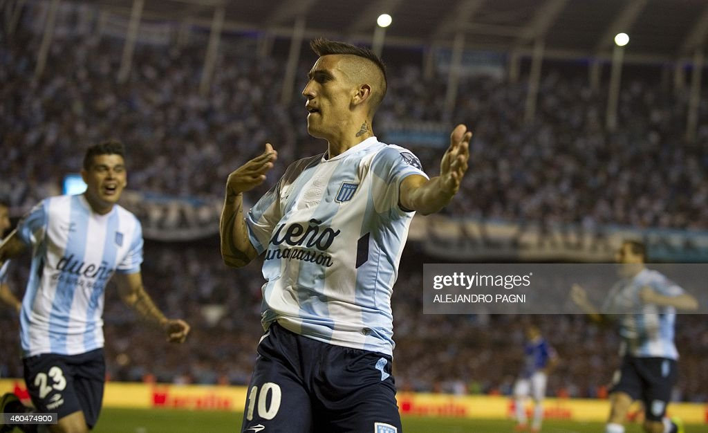 Racing Club's midfielder Ricardo Centurion (C) celebrates after scoring a goal against Godoy Cruz during their Argentine First Division football match, at Presidente Juan Domingo Peron stadium in Buenos Aires, Argentina, on December 14, 2014. AFP PHOTO / Alejandro PAGNI