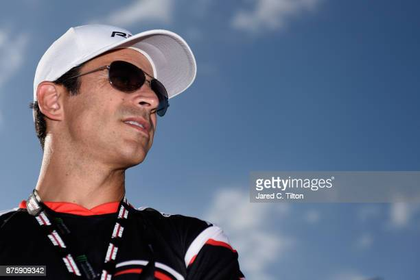 Racing driver Helio Castroneves stands on the grid during prerace ceremonies for the NASCAR XFINITY Series Championship Ford EcoBoost 300 at...