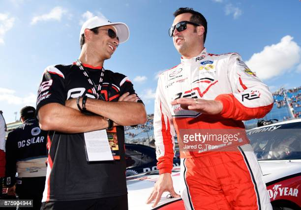 Racing driver Helio Castroneves talks to Sam Hornish Jr driver of the REV/Fleetwood Ford during prerace ceremonies for the NASCAR XFINITY Series...