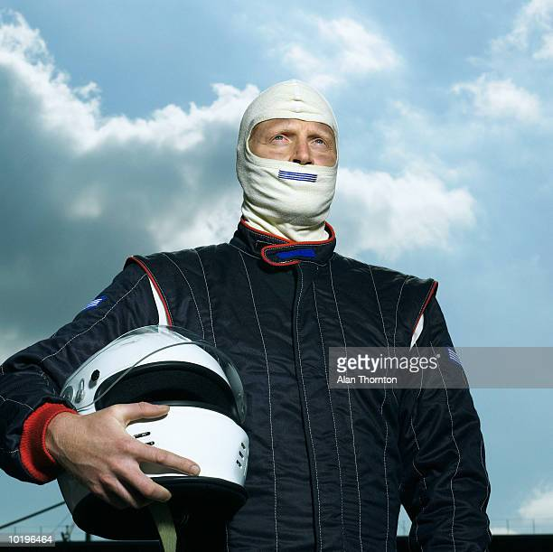 Racing driver holding helmet, close-up