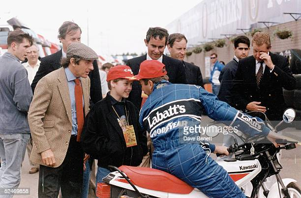 Racing driver Nigel Mansell jokes around with Prince William as Jackie Stewart looks on at the British Grand Prix held at Silverstone race track on...