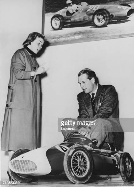 Racing driver Peter Collins team driver for the Scuderia Ferrari plays on a toy replica Ferrari as his wife Louise King watches on 1 April 1957 at...