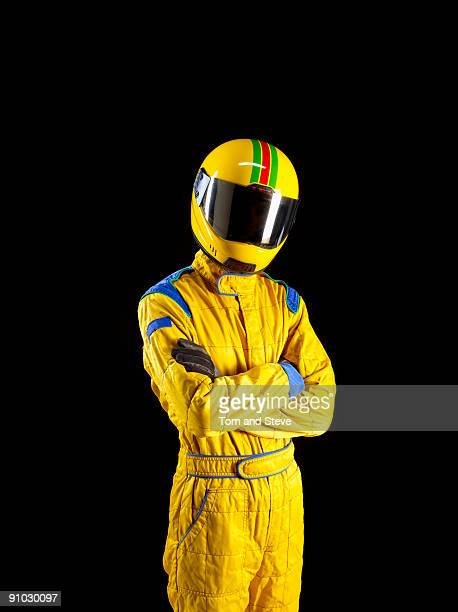 Racing driver standing proud on black background.