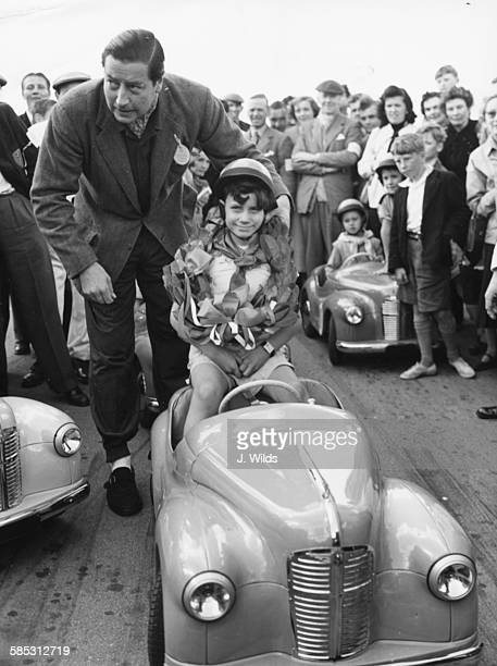 Racing driver Tony Rolt placing the winning garland around the neck of youngster Edward French after he won the Junior Grand Prix at Silverstone...