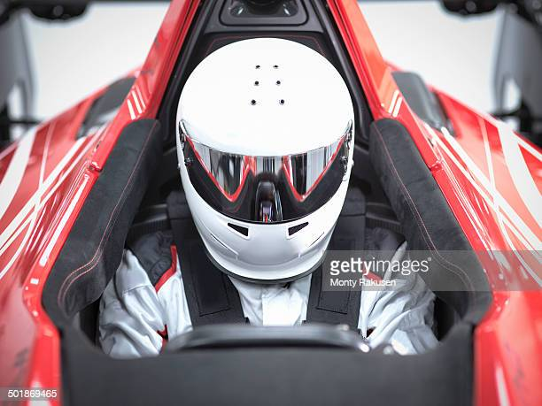 Racing driver wearing crash helmet in supercar