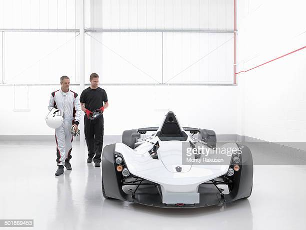 Racing driver with engineer and supercar in car factory