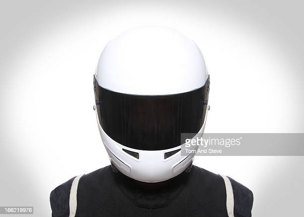 Racing driver with helmet faces camera