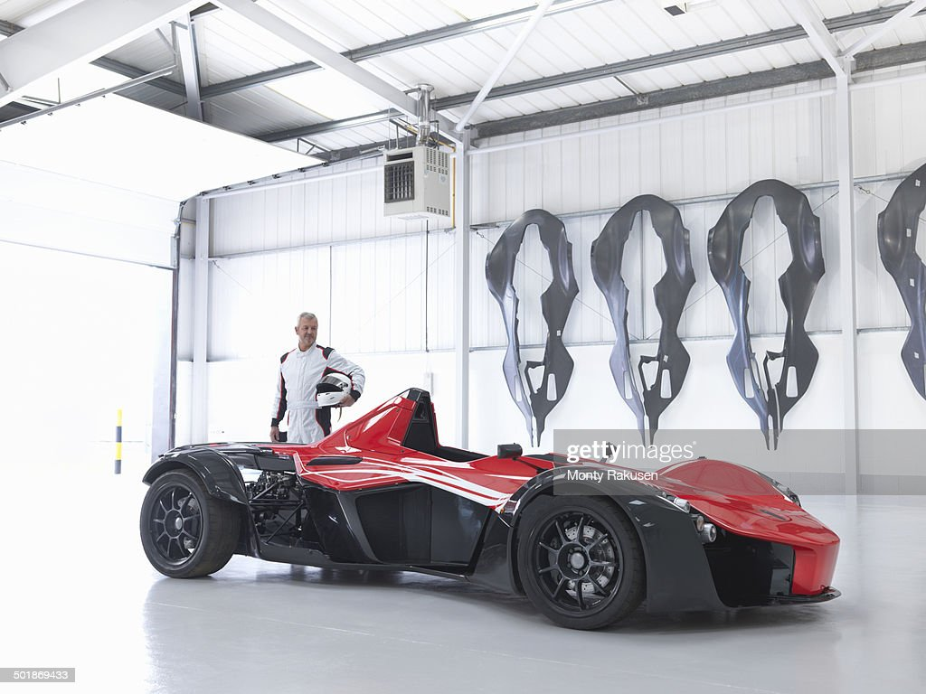 Racing driver with supercar in factory with carbon fibre car body shells on wall