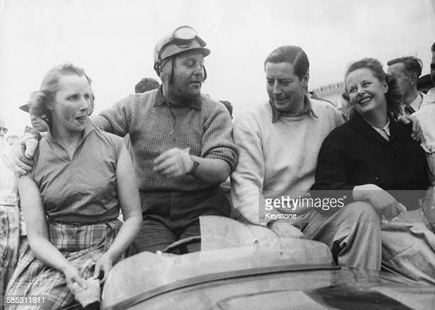 Racing drivers Tony Rolt and Duncan Hamilton with their wives following their victory in the 24 hour Grand Prix d'Endurance in their British Jaguar...