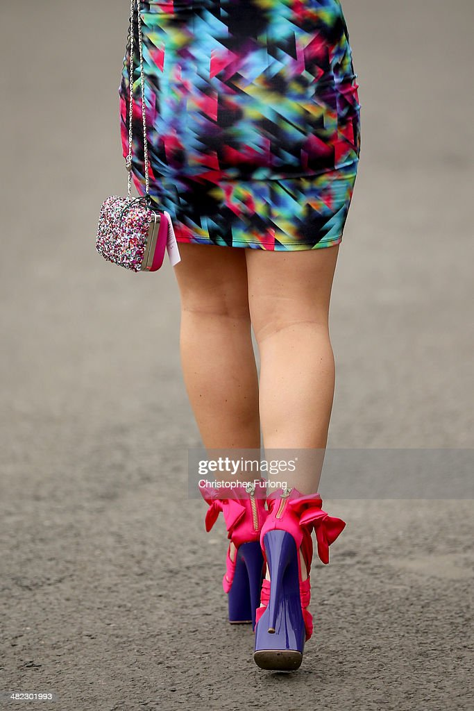 A racing fan in colourful shoes and dress attends the opening day of the Grand National Festival at Aintree Racecourse on April 3, 2014 in Aintree, England. The three days of racing attracts thousands of racegoers and fans from across the world. The meeting culminates with millions of pounds being wagered on the runners taking part in Europe's richest jump race the Grand National.