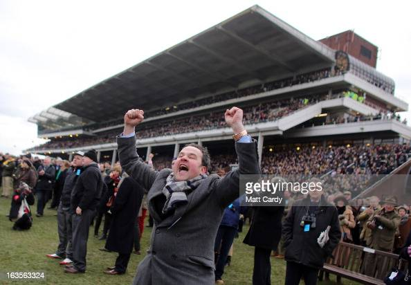 Racing fans celebrate as Ruby Walsh on Hurricane Fly wins The Stan James Champion Hurdle Challenge Trophy during Champion Day at Cheltenham...