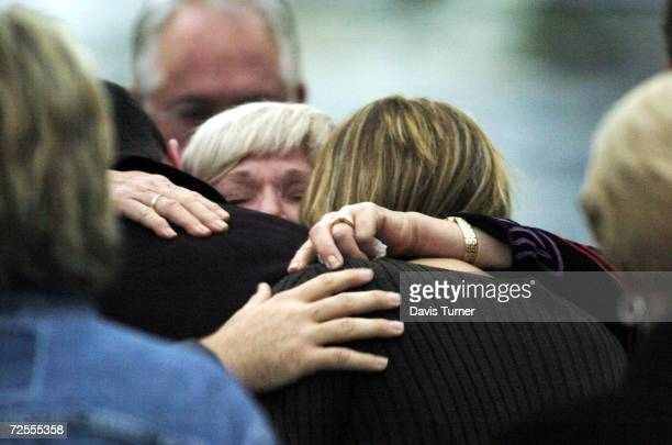 NASCAR racing fans comfort each other as they attend a candlelight vigil at Hendrick Motor Sports October 27 2004 in Charlotte North Carolina Four...