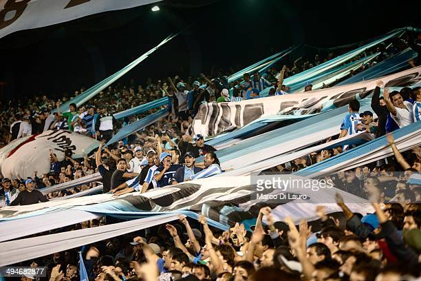 Racing football team fans and 'Barra Brava' hooligans chant slogans to support their team during a match between Racing and Boca Juniors as part of...
