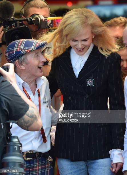 Racing legend Jackie Stewart shares a laugh with Australian actress Nicole Kidman during a visit to the Ferrari gargage ahead of the Formula One...